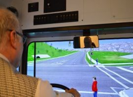An employee demonstrating the use of the bus and snow plow simulator.